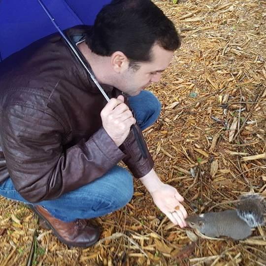 Man with umbrella feeding a gray squirrel.