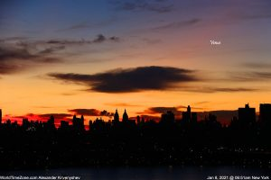 """Colorful sky right before sunrise, with a skyscraper skyline and a bright """"star"""" above."""
