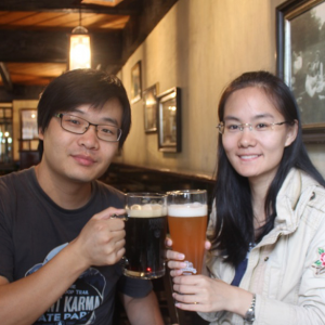 Two young, good-looking Asian people, toasting with mugs of beer.
