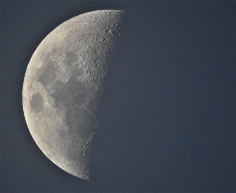 Large left half of moon lit up, right half invisible in dark gray sky.