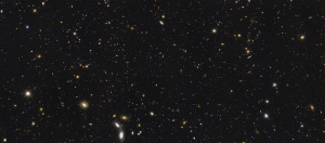 Immensity of multicoloured speckles (galaxies) on black background.