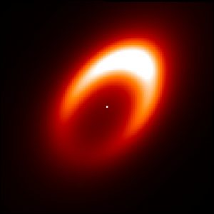 Bright yellowish and whitish ring with white dot in the center, on black background.