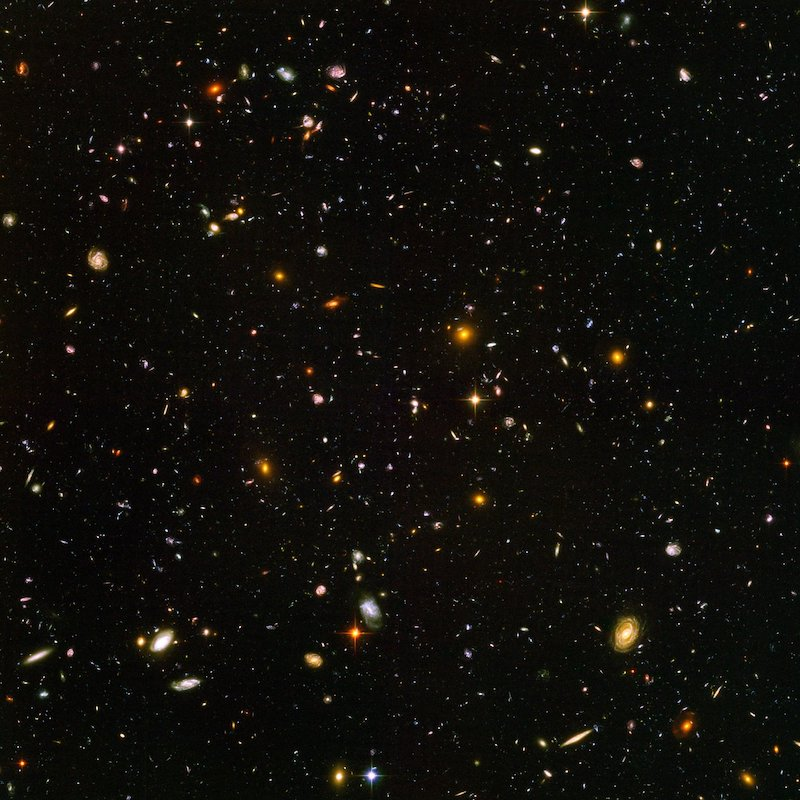 Very many multicolored speckles of light - galaxies - on black background.