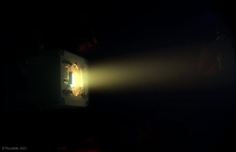 The firing of a spacecraft thruster, sending a yellow stream of exhaust into space.