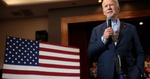 Joe Biden is seen standing in front of the American flag, caught in the middle of a speech.