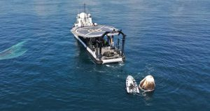 A white, egg shaped spacecraft capsule is seen floating in the ocean water, hauled by a small boat to a larger boat nearby.