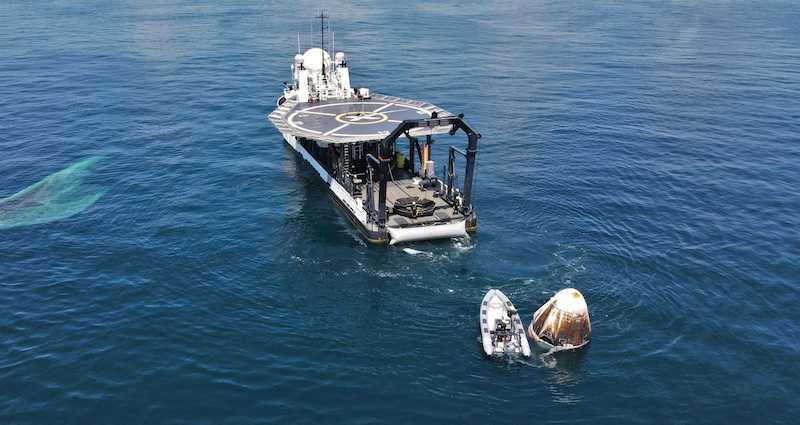A white, egg shaped space capsule floating in the ocean water, hauled by a small boat to a nearby ship.