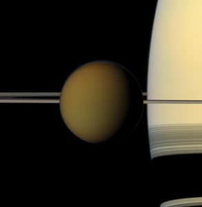 Hazy ball of TItan with Saturn's thin rings behind.