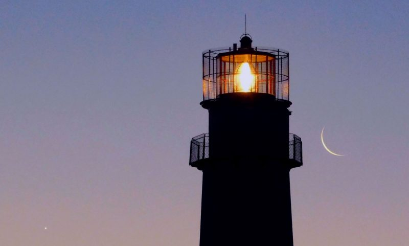 Venus and crescent moon in lavender morning sky on either side of lighthouse.