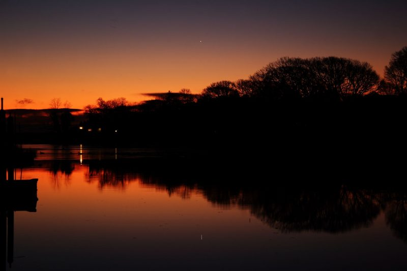 Clear red sky with one bright dot reflected in body of water.