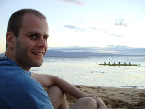 Smiling man sitting on beach with a kayak in the ocean in the distance.