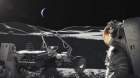 Spacesuited astronauts, next to lunar rover, on stark lunar surface, with Earth in the sky.