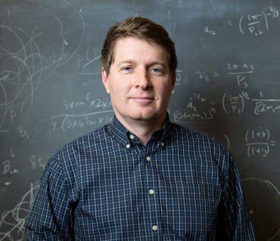 A clean-cut man standing in front of a blackboard.