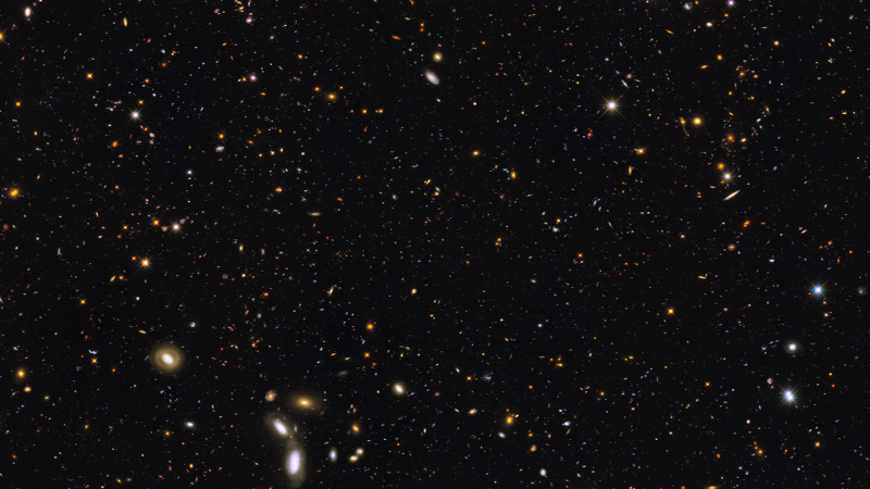 Very many multicolored speckles and tiny ovals (galaxies) on a black background.