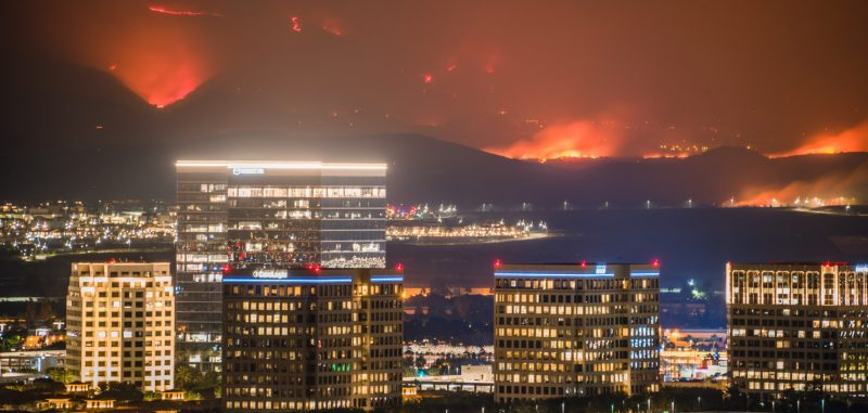 Nighttime cityscape with huge fires in background looking like volcanic eruptions.