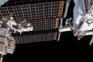 Tiny astronaut between 2 larger parts of a spacecraft against the blackness of space.