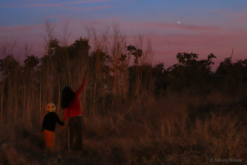 Kids standing in clearing looking at 3 planets in pink sky over forest treetops.