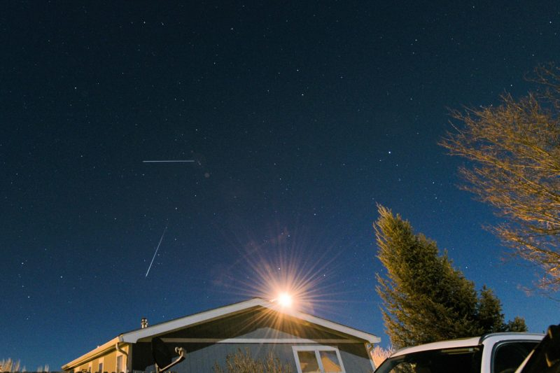 A bright meteor - and a 2nd streak, above it - above a house.