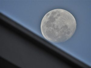 A nearly full moon, rising behind a roofline.