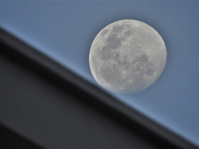 A nearly full moon, rising behind a roofline against a blue sky.
