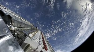 A view from a rocket heading upward, looking down on Earth and a stack of satellites.