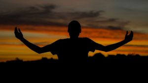 Silhouette of a man with outspread arms and sunset.