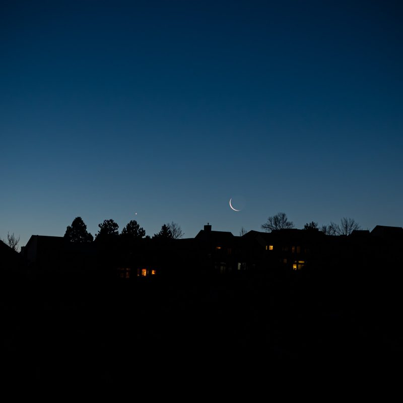 Venus and thin crescent moon in deep blue sky near dark line of silhouetted rooftops.