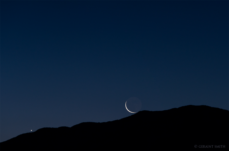 Venus and very thin, bright crescent moon in deep blue sky barely peek over a dark mountain ridge.