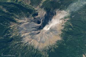 View from orbit of a volcano puffing out a plume of steam.
