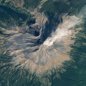View from orbit of a volcano puffing out a plume of steam, ash and rock fragments.