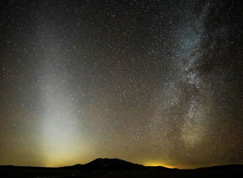 Pyramid-shaped hazy band of zodiacal light, next to a bright section of the starry Milky Way.