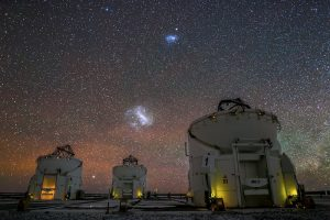 Two irregular glowing fuzzy patches on the sky over several large telescope domes.