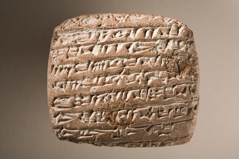 Reddish clay tablet with lines of characters made up of small triangles.