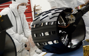 Large, wide black wheel with pattern of holes in it and man in white protective lab suit.