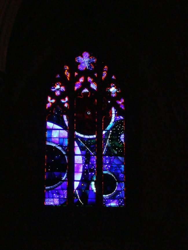 Stained glass window with dark circles and blue rings, pointed arch top.