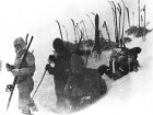 Black-and-white photo of skiers breaking snow, with their skis stashed upright behind them.