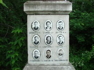 Square stone column with oval photos of 9 people with a name beneath each.