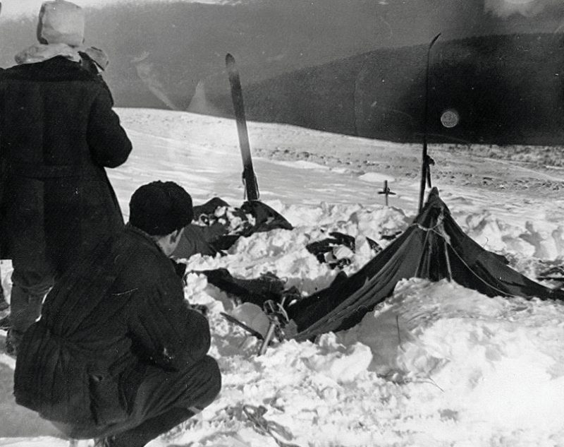 Two searchers look at a ruined tent amid snow.