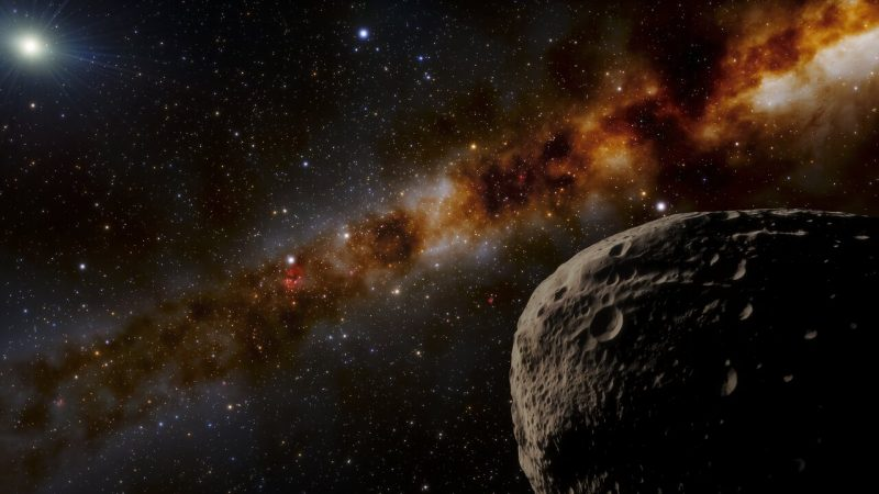Large, cratered rock in space and distant glowing dot with starry band in background.