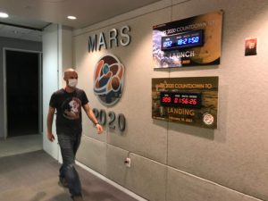 Man with facemask walking down hallway, with mission clocks on the wall.