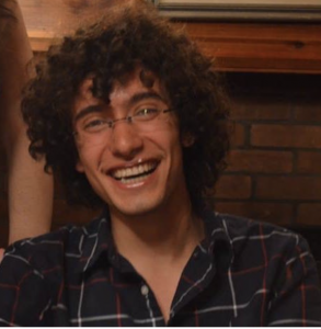 Laughing young man with a lot of curly hair.