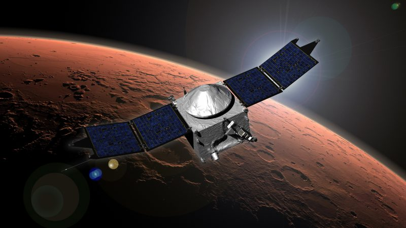 Satellite with two large solar panels above a reddish planet with craters on its surface.