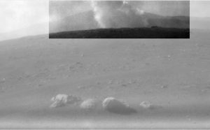 Grayscale photo of rocky landscape with billowing dusty smoke plume rising up from the ground.