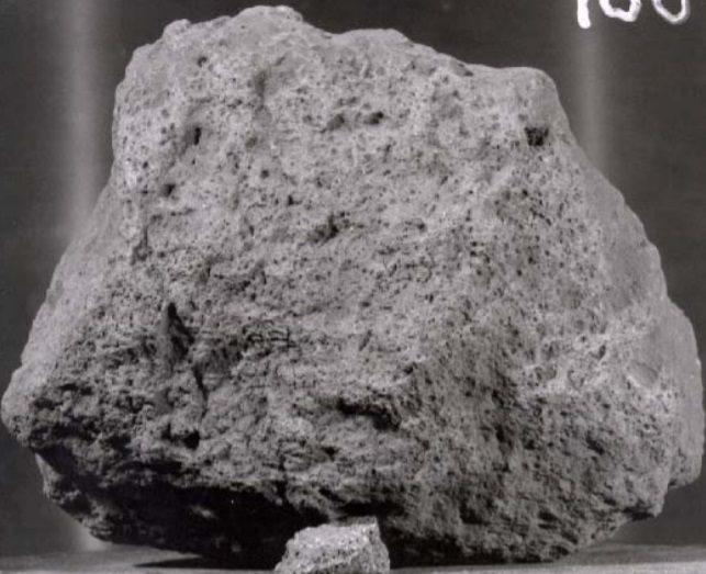 Close up of a light gray, irregular, pitted moon rock.