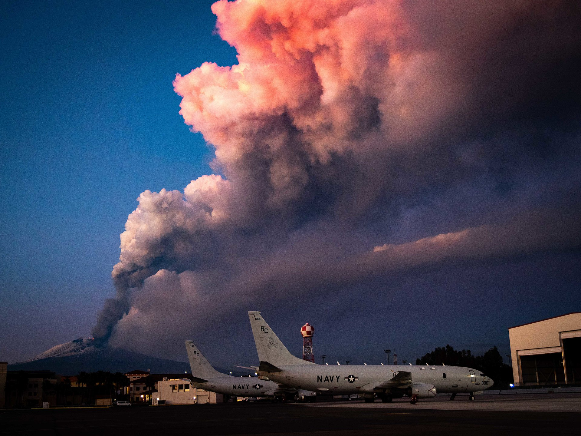 Huge cloud of pink smoke in a blue sky with grounded jet airplanes in foreground.