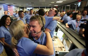 Blue-shirted NASA employees are smiling and embracing in celebration.