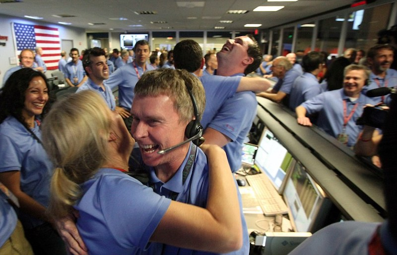 Mavi gömlekli NASA çalışanları gülümsüyor ve kucaklaşıyor.