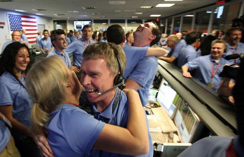 Blue-shirted NASA employees are smiling and celebrating.