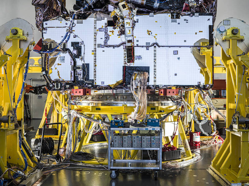 The Webb telescope in a white room with various electrical components exposed while yellow machinery surrounds it.