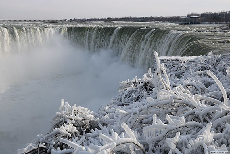 With icy branches in the foreground, water going over a giant waterfall.